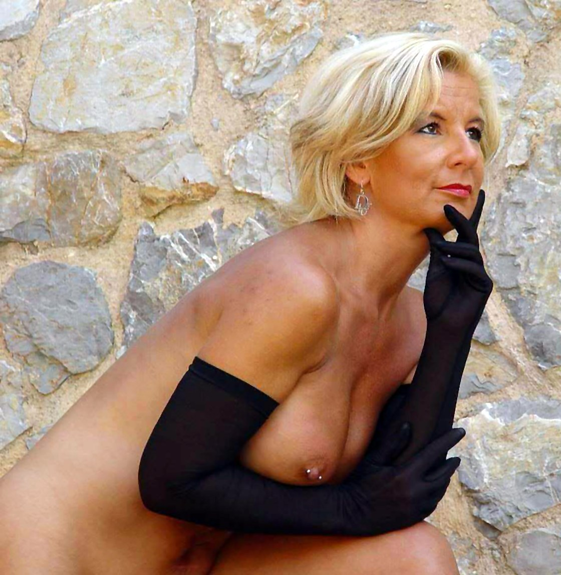 A mature sexy blonde has a pircing in her nipples