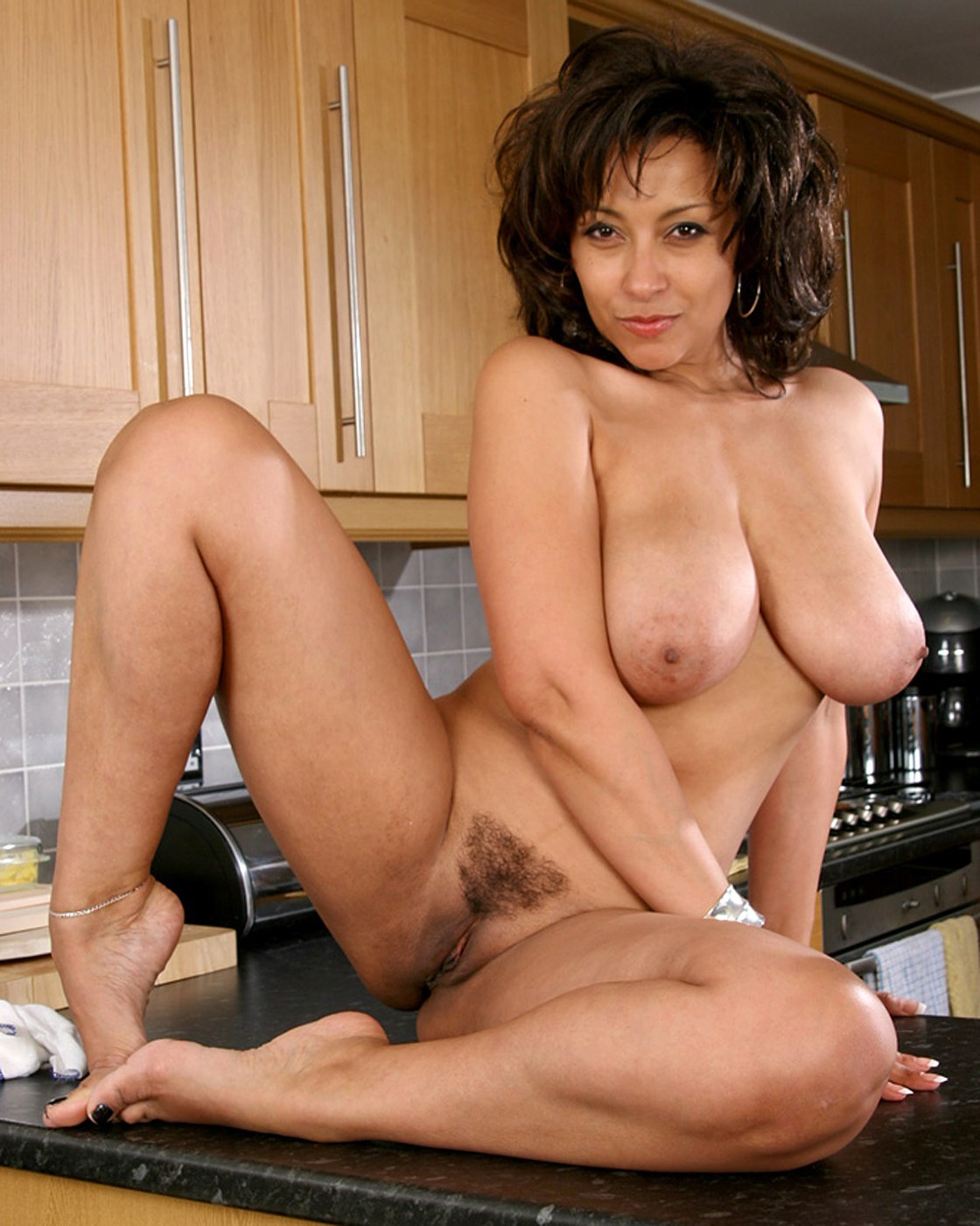 Busty brunette with hairy pussy in kitchen