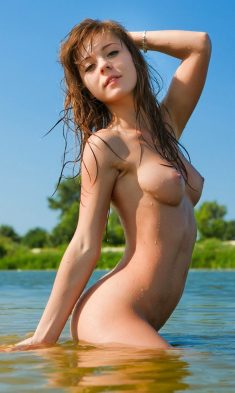 Beautiful girl with solid breasts playing in water