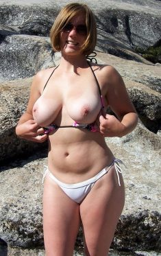 Hot MILF shows her big natural tits in rocks