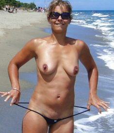 Woman in very revealing bikini on beach