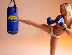 Athletic blonde kickboxer in MMA gloves and panties working out on a heavy bag