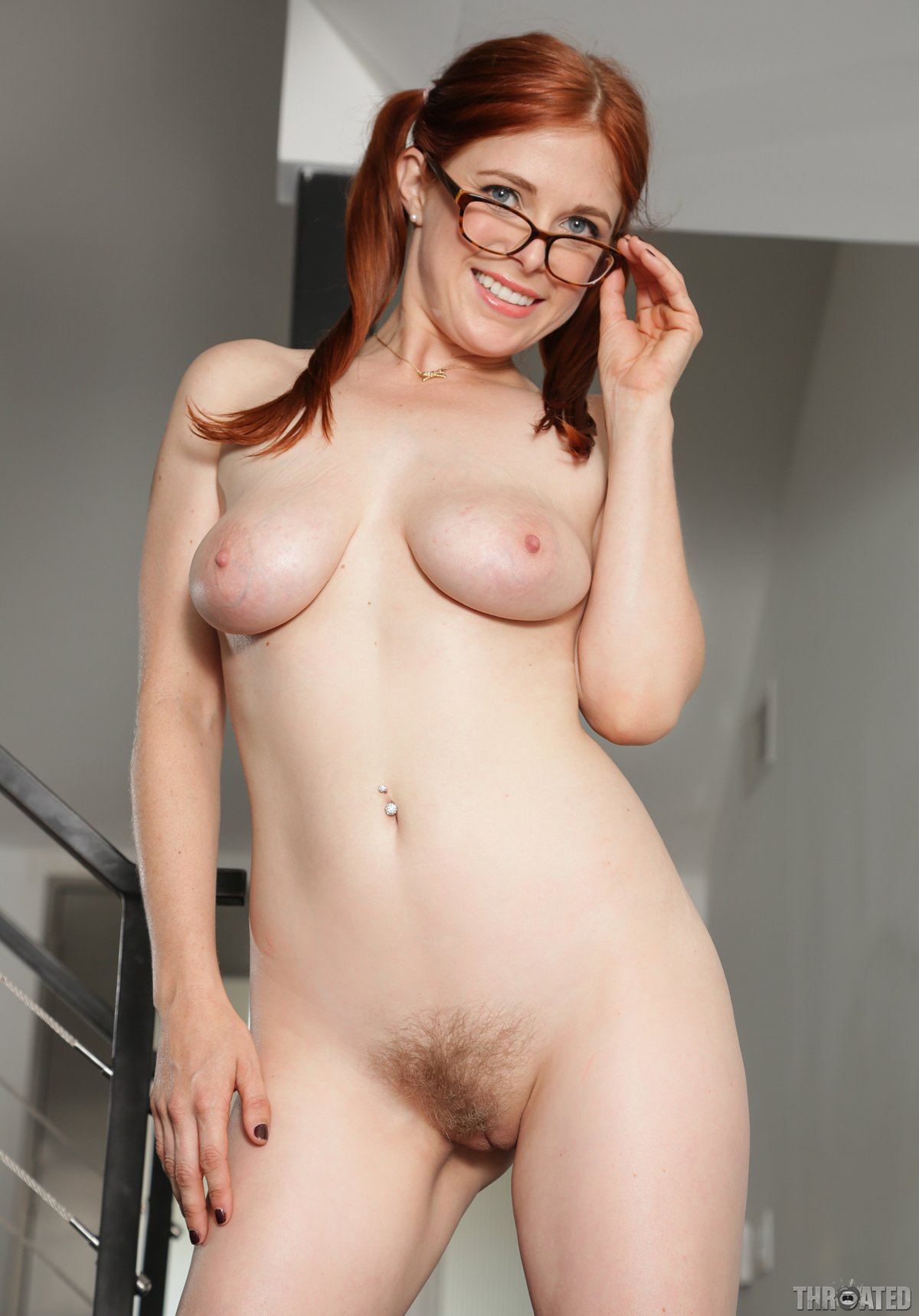 Busty redhead in glasses