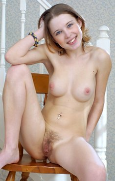 Young cute girl shows a nice hairy pussy on a chair