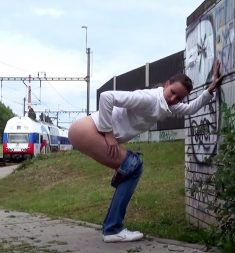 Cute girl pees near the railway