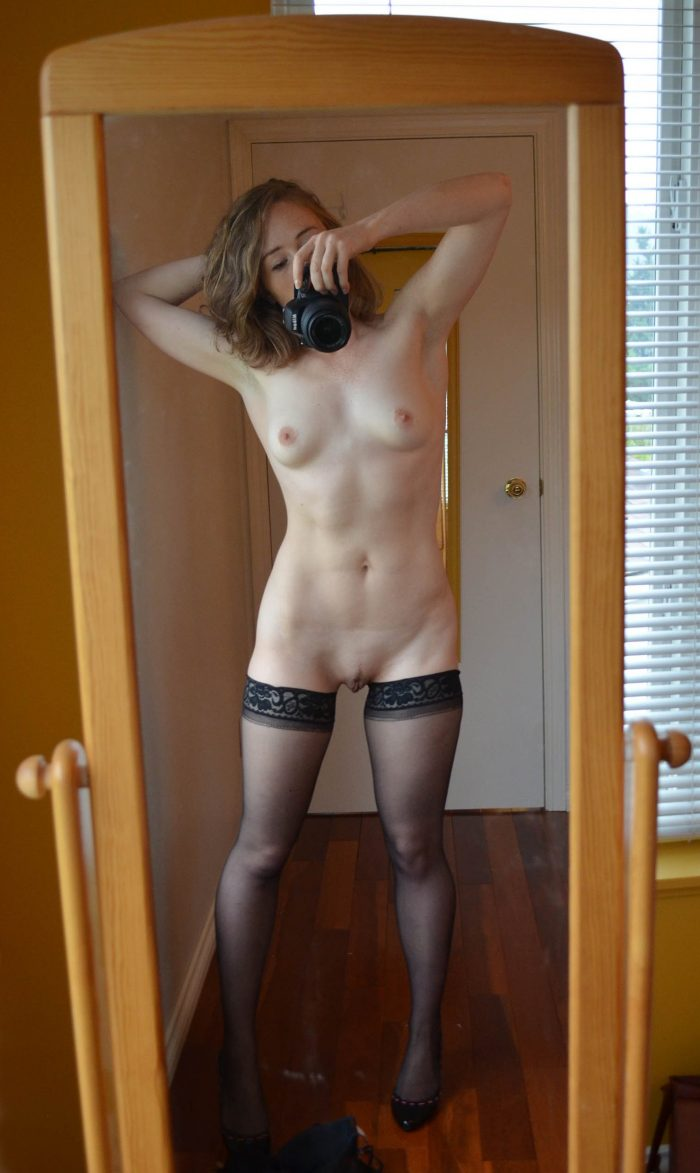 Woman with sexy body doing naked mirror selfie