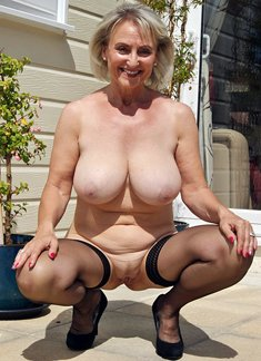 Smiling older woman reveals her big naturals boobs