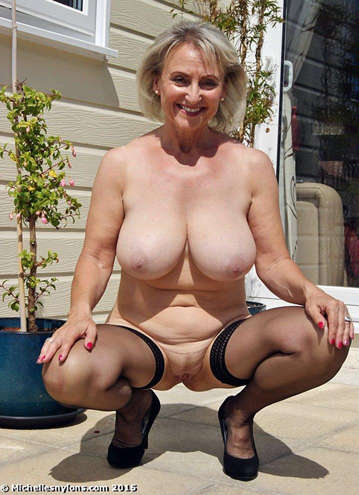 Smiling older woman reveals her big naturals boobs