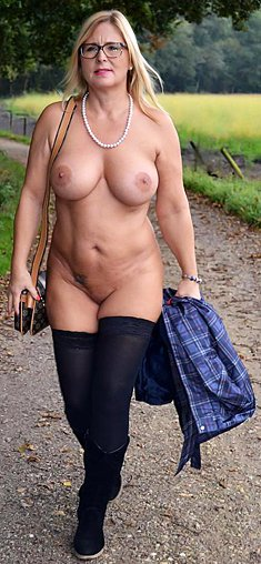 Mature woman with big tits Chrissy in glasses walks naked in the rain
