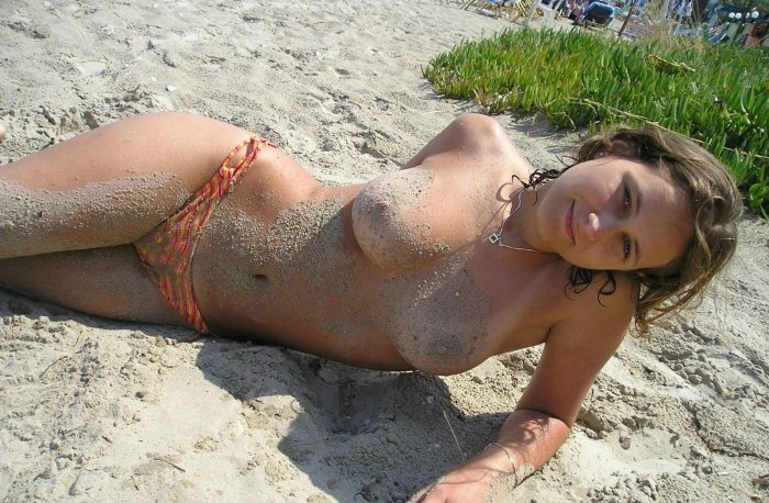 Topless girlfriend smiling on the beach