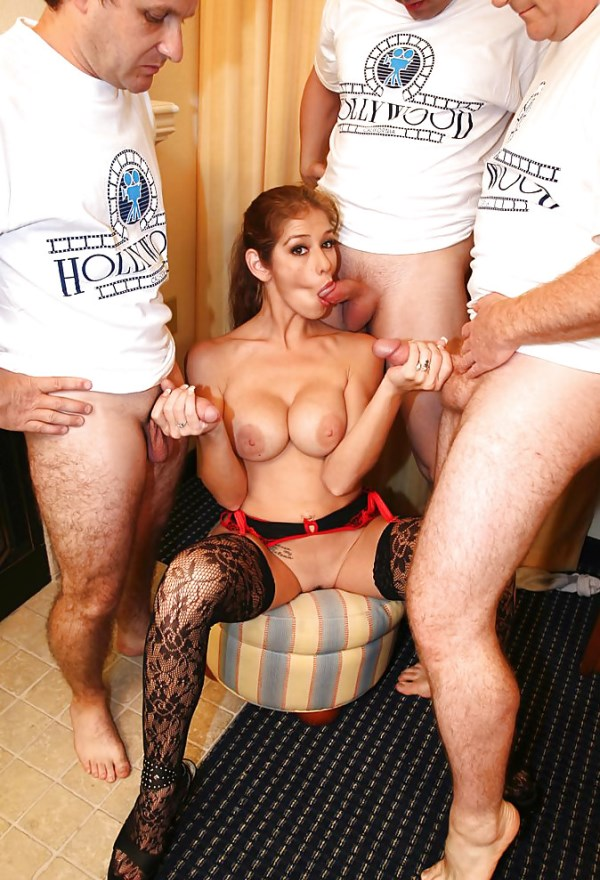 Babe with big fake tits serve three cocks to blowjobs and handjobs