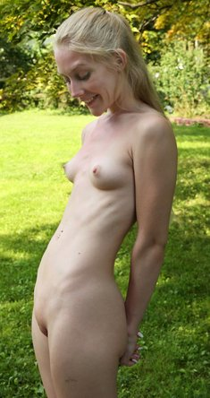 Blonde Emma Starletto shows off her flexibility while naked in the yard