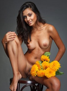 Lovely girl Adrienne puts down a bunch of flowers while modeling in the naked