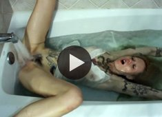 Tattooed girl masturbates in the bath using running water