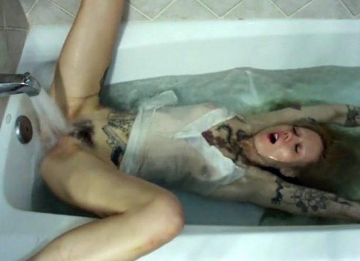Tattooed girl masturbates in the bath using running water