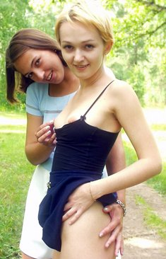 Young lesbians exposes themselves and lick nipples while on a path in the woods
