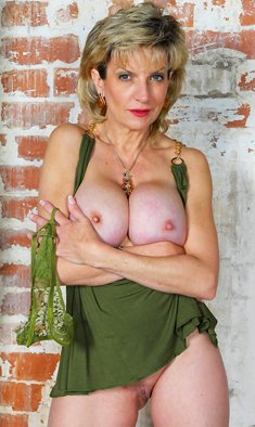 Mature blonde Lady Sonia releases her big boobs from her short dress