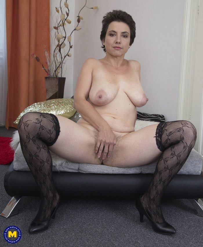 Mature busty brunette Ailana inserts a dildo into her hairy pussy