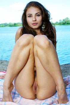 Beautiful brunette girl posing naked outside by the lake