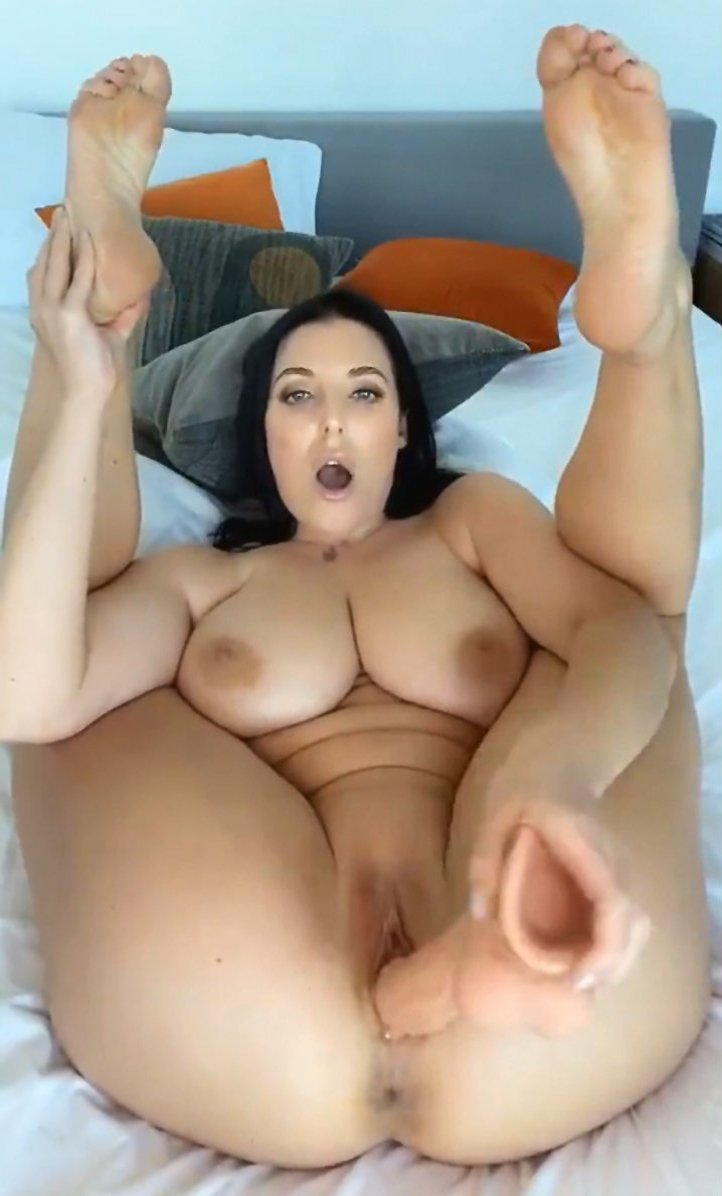 Busty brunette masturbates with a big dildo on the bed