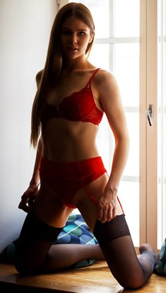 Evelina on the window in red lingerie