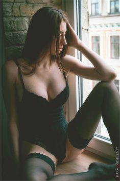 Lina in sexy lingerie poses on the window
