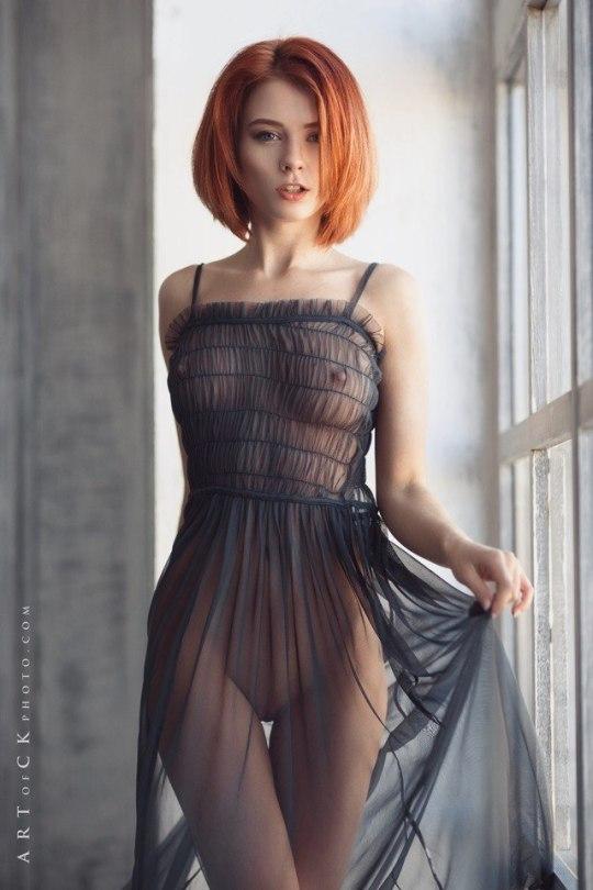 A hot redhead in a transparent dress