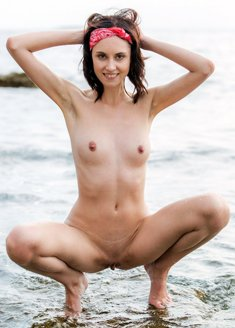 Lovely slim babe Sade Mare strips in the sea and poses butt naked
