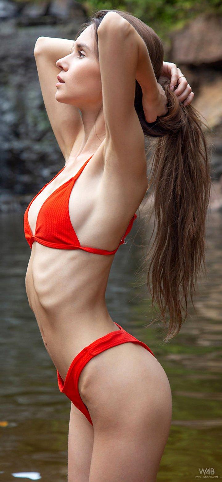 Slim girl Leona Mia takes off her red bikini outdoors