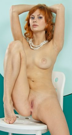 Redhead Angela D uncovers her medium breasts and sweet pussy