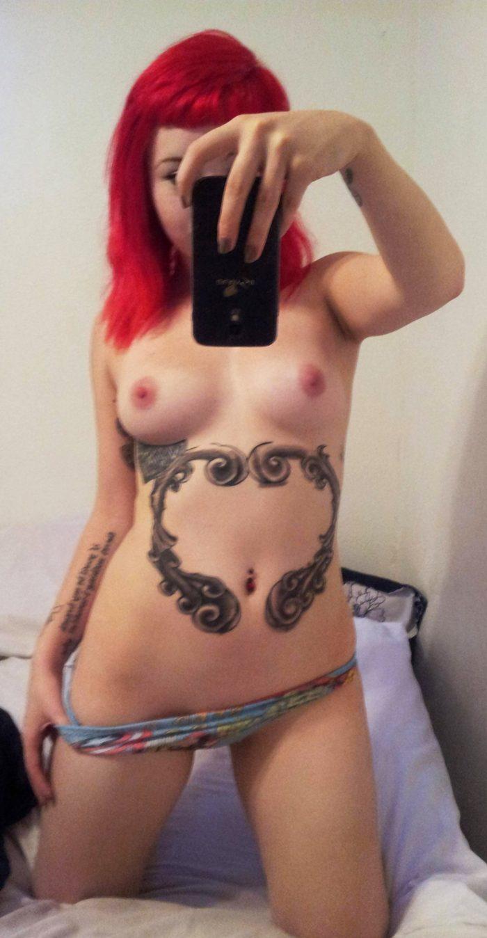 Tattooed redhead girl makes selfie topless