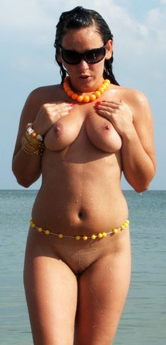 Gorgeous busty brunette in sunglasses posing naked on the beach