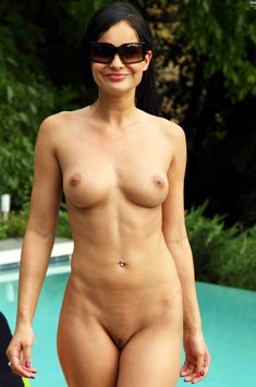 Sensual brunette completely naked outside by the pool