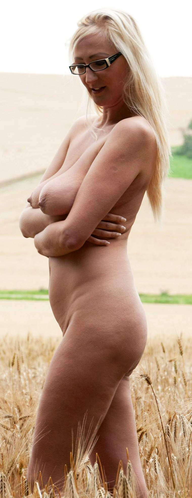 A beautiful busty blonde is walking naked in a cereal field